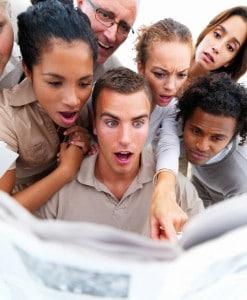 Surprised business people reading newspaper