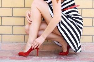 אשה בשמלה קצרה עם נעל אדומה